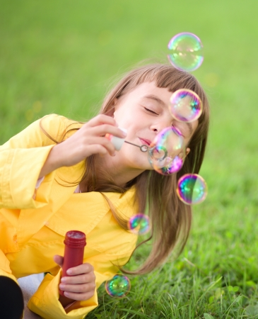 Portrait of cute girl blowing soap bubbles photo