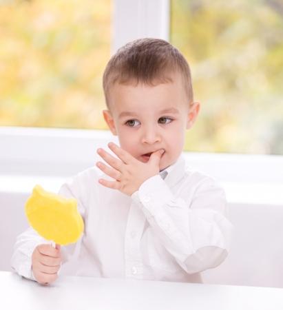 Happy little boy with big lollipop photo