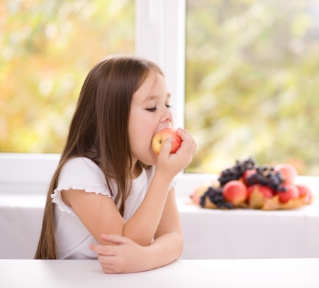 Cute little girl eating an apple photo