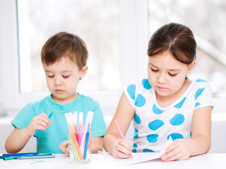 Little children is drawing on white paper using color pencils photo