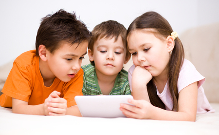 Happy children using tablet computer photo