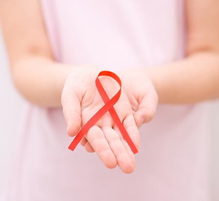 Healthcare and medicine concept - girl hands holding red breast cancer awareness ribbon photo