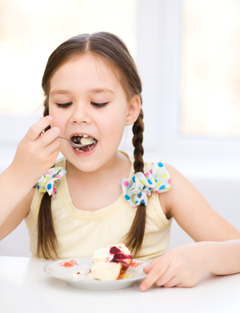 Cute little girl is eating ice-cream photo