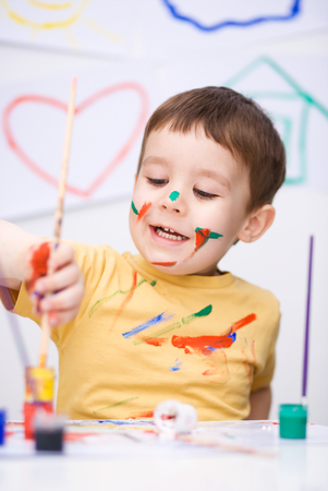 Portrait of a cute little boy playing with paints photo