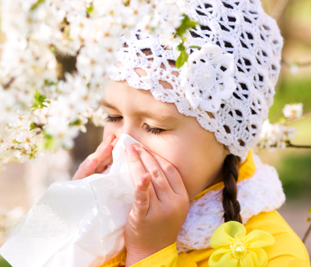Spring portrait of a little girl is blowing her nose Stock Photo