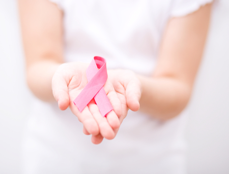 healthcare and medicine concept - girl hands holding pink breast cancer awareness ribbon photo