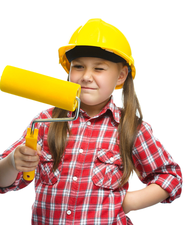 Happy cute girl as a construction worker with paint roller, isolated over white photo