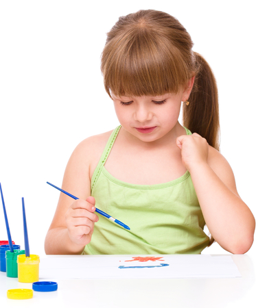 Cute thoughtful child play with paints while sitting at table, isolated over white photo
