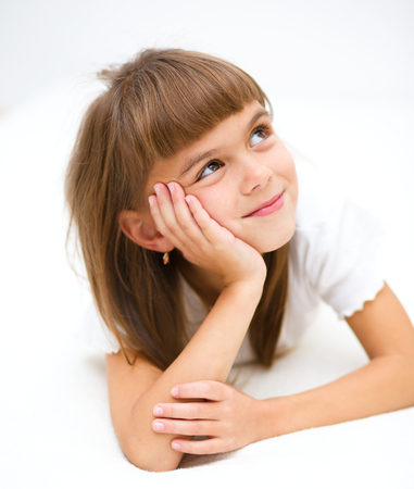 and guessing: Little girl is daydreaming lying on the floor Stock Photo