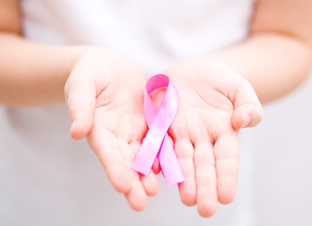 nice breast: healthcare and medicine concept - girl hands holding pink breast cancer awareness ribbon