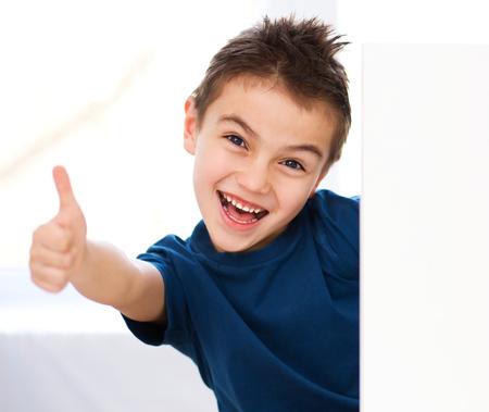 Little boy is holding blank banner