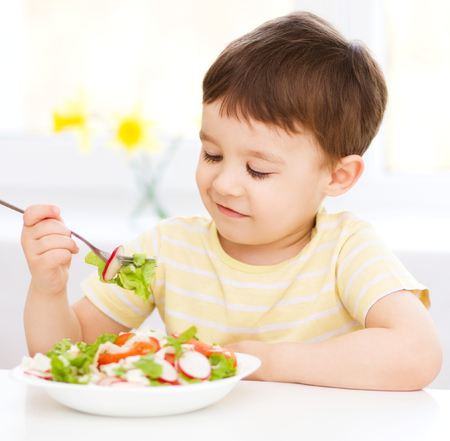 children eating: Cute little boy eats vegetable salad using fork Stock Photo