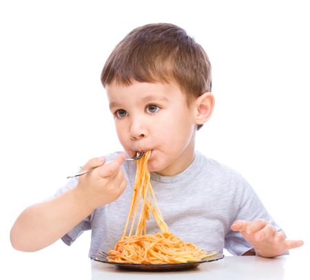 Kleine jongen is het eten van spaghetti met vork, geïsoleerd over white