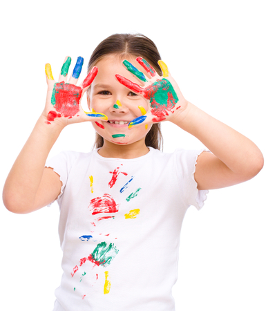 Cute girl showing her hands painted in bright colors, isolated over white