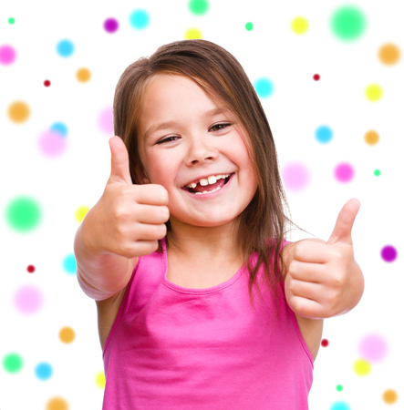 Cute girl is showing thumb up gesture using both hands, over color background Stock Photo