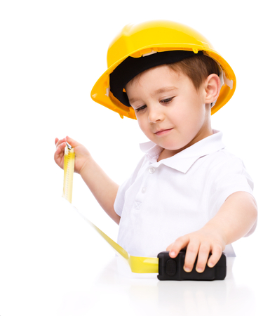 Happy cute boy as a construction worker with tape measure, isolated over white photo