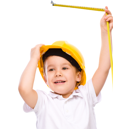 Happy cute boy as a construction worker with tape measure, isolated over white Stock Photo