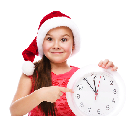 santa helper: Christmas, winter, time and people concept - girl in santa helper hat with clock, isolated over white