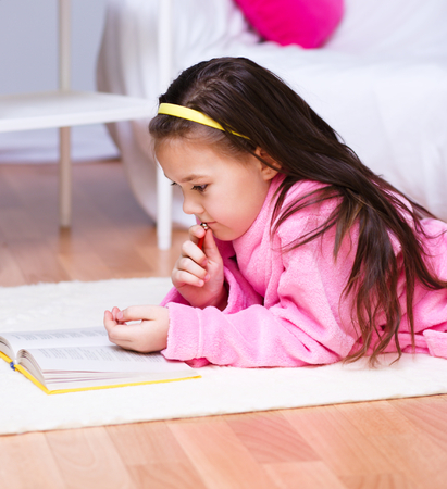erudition: Cute little girl is reading a book Stock Photo