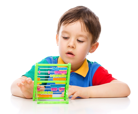 young  brunette: Cute little boy is playing with building blocks, isolated over white