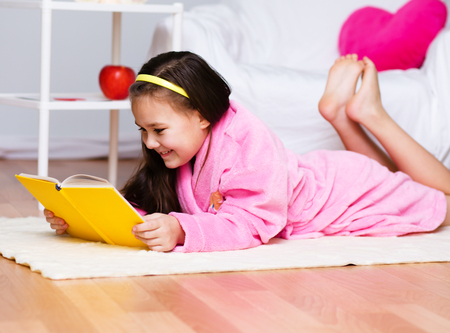 erudition: Cute girl is reading a book Stock Photo