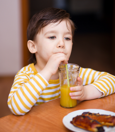 Little boy is drinking orange juice using straw photo