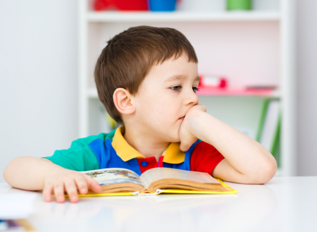 erudition: Cute little boy is reading book while sitting at table, indoor shoot