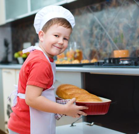 haciendo pan: Muchacho lindo que hace el pan en la cocina Foto de archivo