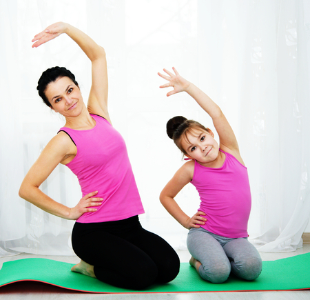 Cute mother and daughter doing exercise home Standard-Bild
