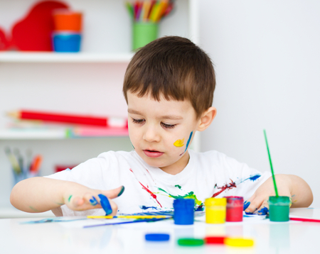 child education: Portrait of a cute little boy playing with paints