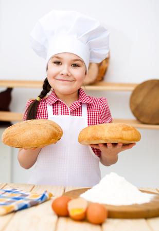 making bread: Cute girl fare il pane in cucina