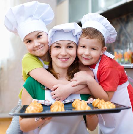 making bread: Madre con i bambini felici che fanno il pane in cucina