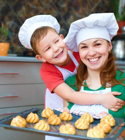 haciendo pan: Madre con el ni�o feliz haciendo pan en la cocina