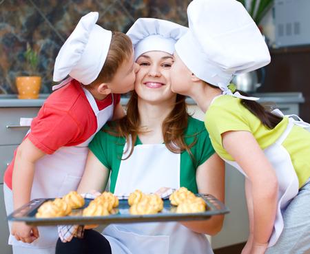 haciendo pan: Madre con los ni�os felices haciendo pan en la cocina