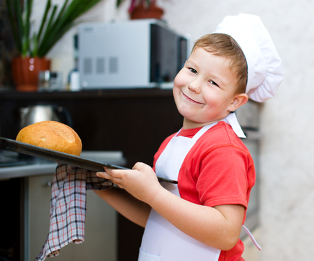 Cute boy making bread in the kitchen Stock Photo