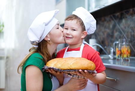 haciendo pan: Madre feliz con el hijo hacer pan en la cocina