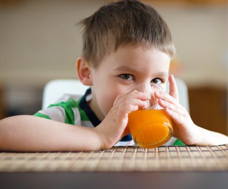 vaso de jugo: El ni?o peque?o est? bebiendo jugo de naranja con paja Foto de archivo