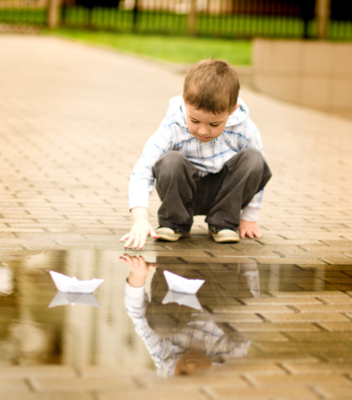 tar paper: Cute little boy is playing with paper boat