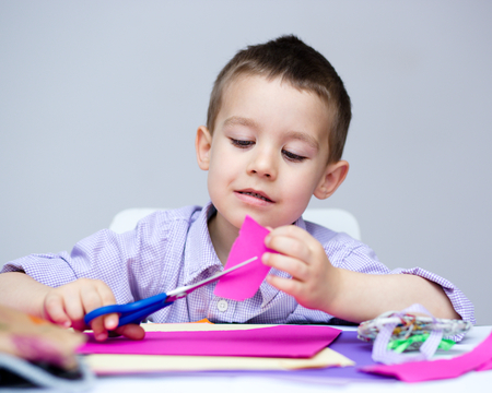 scissors cutting paper: Little smiling boy is cutting paper using scissors Stock Photo