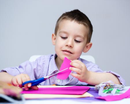 tijeras: Pequeño muchacho sonriente está tijeras de corte de papel utilizando