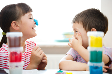niños en la escuela: Niños felices que juegan con el juego de colores de masa