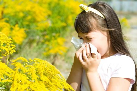 少女は、彼女の鼻、咲く花にアレルギーを吹いています。