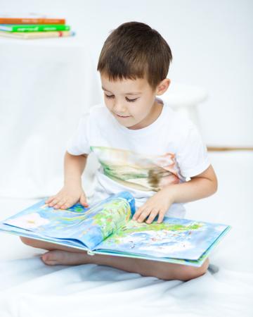 Cute little boy is reading book