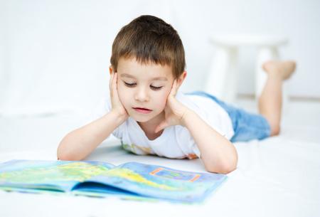 kids reading book: Cute little boy is reading book