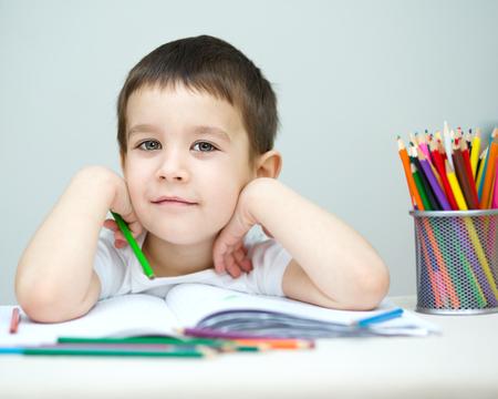 jovenes felices: El niño pequeño está sosteniendo montón de lápices de colores