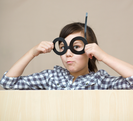 astounded: Funny girl with fake glasses. Happy child playing in home Stock Photo