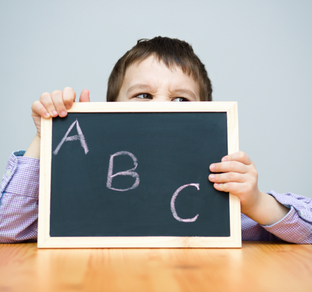erudition: Cute boy is holding blackboard - education concept