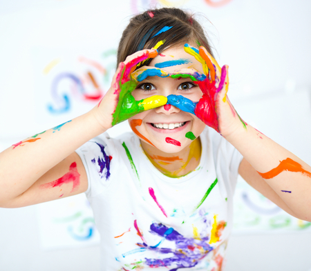 kinder: Muchacha linda que muestra sus manos pintadas en colores brillantes Foto de archivo