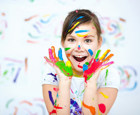 Cute girl showing her hands painted in bright colors Stock Photo