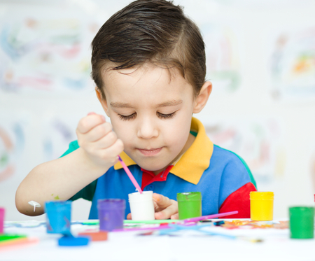 child drawing: Portrait of a cute little boy playing with paints